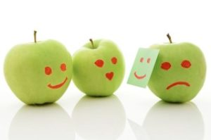 Two green apples, smiling and crying on white.